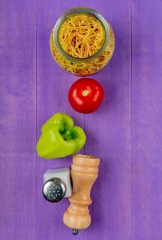Vista verticale di maccheroni degli spaghetti con il sale del pepe del pomodoro sulla tavola porpora