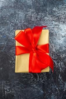 Vista verticale del regalo speciale con nastro rosso su superficie scura dark