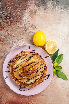 Vertical view of stuffy pancakes decorated with chocolate syrup and lemon on colourful table
