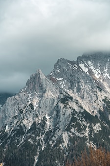 Vertical view of a tall mountain under the cloudy sky