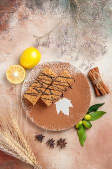 Vista verticale di gustosi dessert decorati con cioccolato syrop e limone sul tavolo colorato