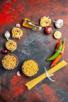 Vista verticale della gustosa preparazione per la cena con pasta cruda in varie forme e aglio olio caduto bottiglia aglio limone su sfondo di colore misto