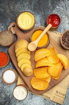 Vista verticale di gustose patatine fatte in casa tagliate fette di patate sul tagliere di legno e diverse spezie sul giornale su sfondo grigio