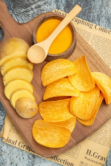 Vertical view of tasty homemade chips cut potato slices on wooden cutting board on newspaper on gray background