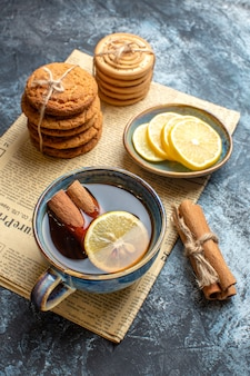 Vertical view of tea time with stacked delicious cookies cinnamon lemon on an old newspaper on dark background
