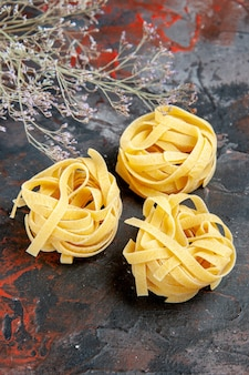 Vertical view of three uncooked spaggeties on mixed color background