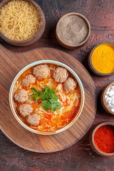 Vertical view of tomato meatballs soup with noodles in a brown bowl and different spices on dark background