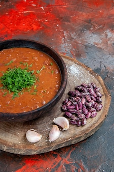 Vertical view of tomato soup beans garlic on wooden cutting board on mix color background