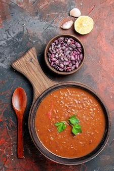 Vertical view of tomato soup beans and lemon on cutting board on a mixed color background