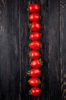Vista verticale della linea di pomodori sulla tavola di legno