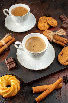 Vertical view of two cups of coffee cookies cinnamon limes chocolate bars on wooden cutting board on dark background