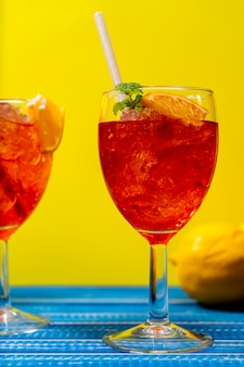 Vertical view of two glasses of the refreshing aperol spritz cocktail with mint