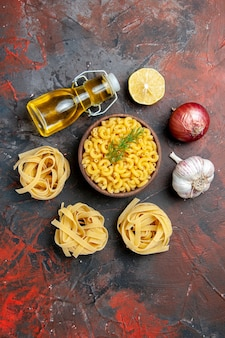 Vertical view of uncooked three spaggeties and butterfly pastas in a brown bowl and green onion lemon garlic oil bottle on mixed color background