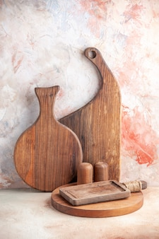 Vertical view of various kinds of wooden chopping boards standing on colorful surface