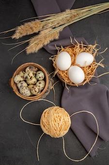 Vertical view of various organic eggs in a brown pot rope spike black towel on dark background