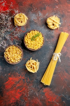 Vertical view of various types of uncooked pastas on mixed color background