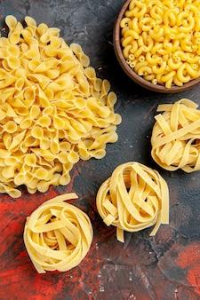 Vista verticale di vari tipi di pasta cruda su sfondo di colore misto