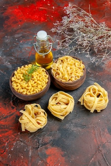Vertical view of various types of uncooked pastas and oil bottle on mixed color background