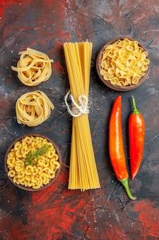 Vista verticale di vari tipi di pasta cruda e peperoni su sfondo di colore misto