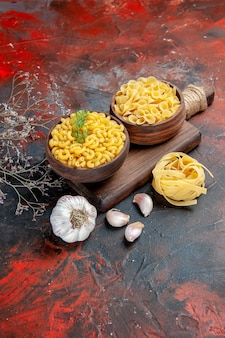 Vertical view of various types of uncooked pastas on wooden cutting board and garlic on mixed color background