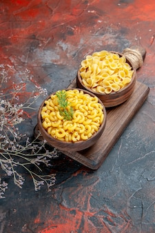 Vertical view of various types of uncooked pastas on wooden cutting board