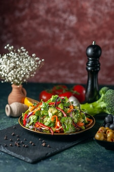 Vista verticale di insalata vegana con ingredienti freschi in un piatto su tagliere nero