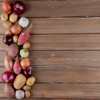 Vertical view of vegetables as radish onion garlic potato on wooden background with copy space