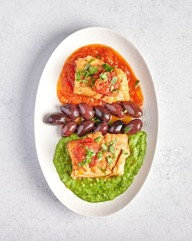 Vertical view white fish with olives, pesto and sauce of tomatoes and baked peppers on white oval plate, food style concept, close up, copy space