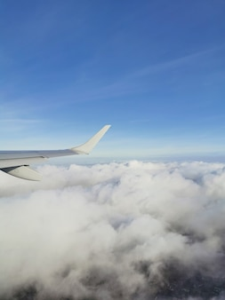 Vertical view of white fluffy clouds in the blue sky under the wing of the plane