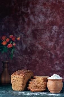 Vista verticale di pane nero dietetico intero tagliato e farina in vaso di fiori su sfondo blu marrone rossiccio