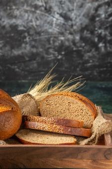 Vista verticale di pane nero fresco intero e tagliato in una scatola di legno marrone sulla superficie di colori scuri