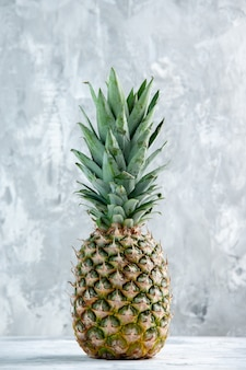 Vertical view of whole fresh golden pineapple standing on marble surface