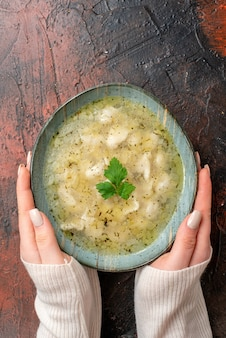 Vista verticale della mano della donna che tiene la zuppa di dushbere di gnocchi stagionali azerbaigiani servita con verde in una pentola su superficie scura