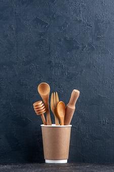 Vista verticale di cucchiai da cucina in legno in una caffettiera di plastica su parete scura