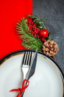 Vista verticale dello sfondo di natale con set di posate con nastro rosso su un piatto da pranzo accessori per la decorazione rami di abete su un tovagliolo rosso