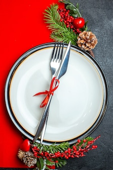 Vertical view of xsmas background with cutlery set with red ribbon on a dinner plate decoration accessories fir branches on a red napkin