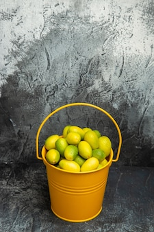 Vista verticale di un secchio giallo pieno di mandarini verdi freschi su sfondo grigio
