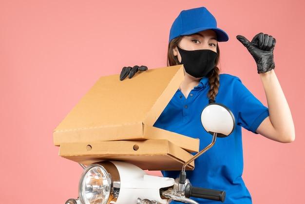 Vista verticale del giovane corriere femminile fiducioso che indossa maschera medica e guanti che aprono scatole che puntano indietro sulla pesca pastello