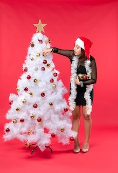 Vista verticale della giovane donna in un abito nero con cappello di babbo natale e decorare l'albero di capodanno sul rosso