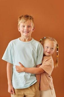 Vertical waist up portrait of cute girl with down syndrome hugging older brother while standing against plain brown surface in studio