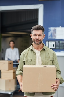 Vertical waist up portrait of handsome man holding box and  while standing by self storage facility