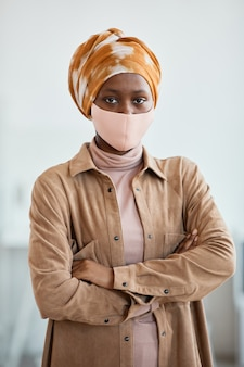 Vertical waist up portrait of modern african-american woman wearing mask and looking at camera while standing in office