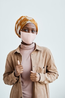 Vertical waist up portrait of modern african-american woman wearing mask and looking at mwhile standing against white wall