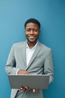 Вертикальная талия портрет современного афро-американского бизнесмена, держащего ноутбук и улыбающегося в камеру, стоя у синей стены в офисе, скопируйте пространство выше