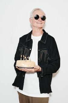 파티에서 흰색 배경에 생일 케이크를 들고 있는 멋진 노인의 세로 허리 위 초상화, 플래시로 촬영