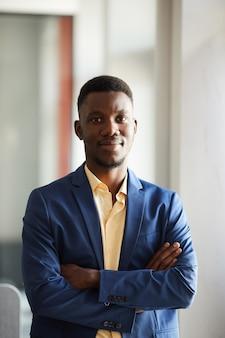 Вертикальная талия вверх портрет элегантного африканского бизнесмена, смотрящего в камеру, уверенно позирующего, стоя со скрещенными руками в интерьере современного офиса, копией пространства