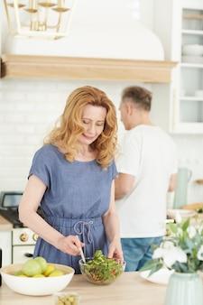 백그라운드에서 남편과 함께 부엌에서 요리를 즐기면서 샐러드를 혼합 우아한 성숙한 여자의 세로 허리 위로 초상화, 복사 공간