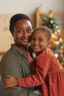 小さな女の子を抱いて、家でクリスマスを楽しみながらカメラを見ている幸せなアフリカ系アメリカ人の母親の垂直ウエストアップの肖像画