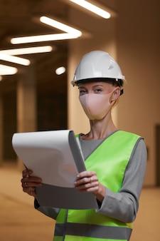 마스크를 착용하고 실내 건설 현장에서 클립 보드와 함께 서있는 동안 성숙한 여성 노동자의 초상화를 수직 허리 위로