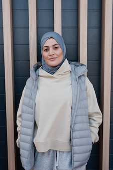 街の壁に向かってポーズをとっている間、ヘッドスカーフを身に着けて、カメラを見ている現代の中東の女性の垂直ウエストアップの肖像画